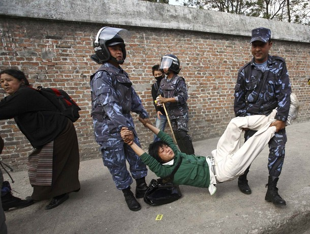 Police arrest a protester near the Chinese Embassy Consular Office in Kathmandu